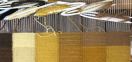 closeup of the tapestry loom with a gold toned tapestry iwork in process