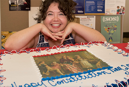 "Woman in front of ""Constitution Day"" cake"